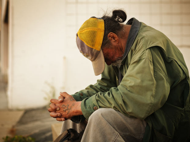 homeless man with head bowed