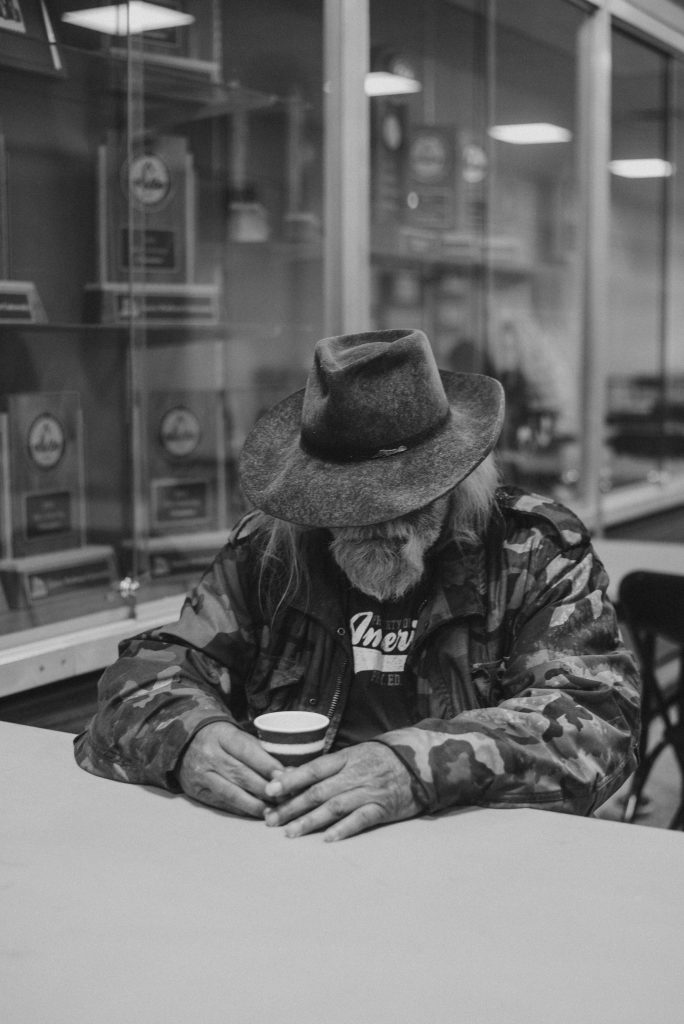 A homeless man is seated at a shelter table. Picture used by permission- Open Doors.